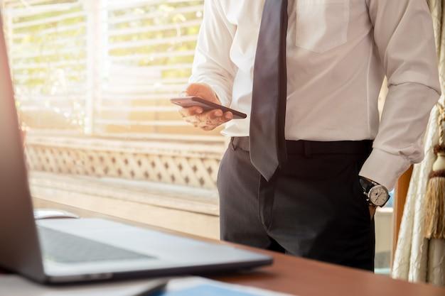 Geschäftsmann, der handy mit laptop auf hölzernem schreibtisch betrachtet.