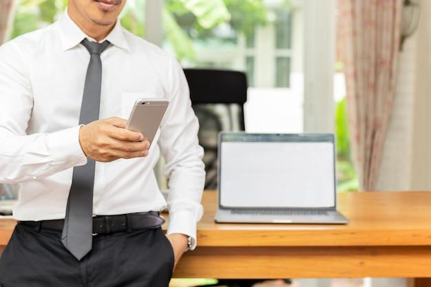 Geschäftsmann, der handy mit laptop auf holztisch im büro betrachtet