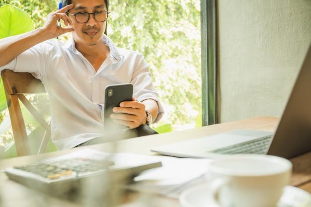 Geschäftsmann, der handy mit laptop und taschenrechner auf tisch betrachtet.