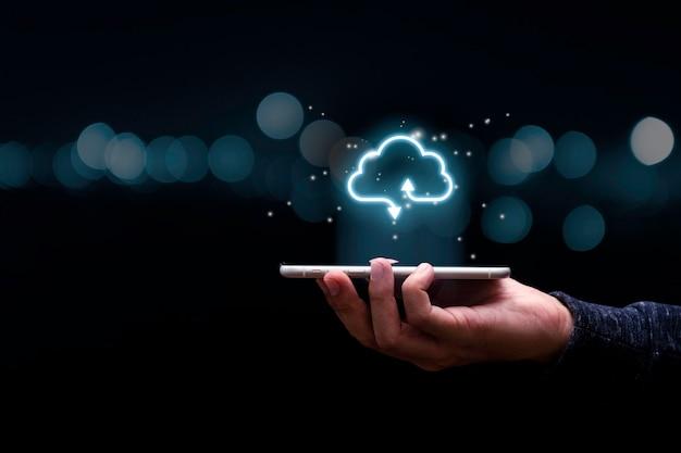 Geschäftsmann, der handy mit virtuellem cloud-computing hält, um dateninformationen zu übertragen und download-anwendung hochzuladen. konzept der technologietransformation.