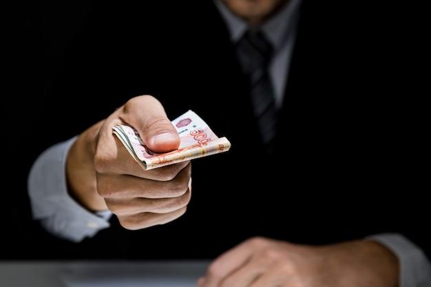 Geschäftsmann, der heimlich geld in der dunkelheit gibt