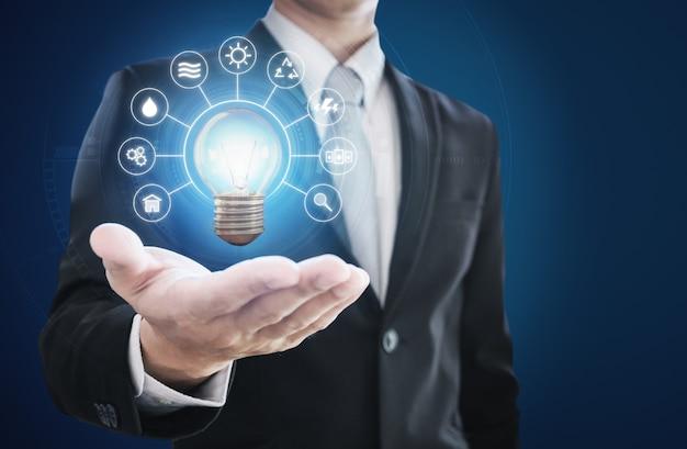 Geschäftsmann, der helle glühbirne mit energieressourcenikone hält