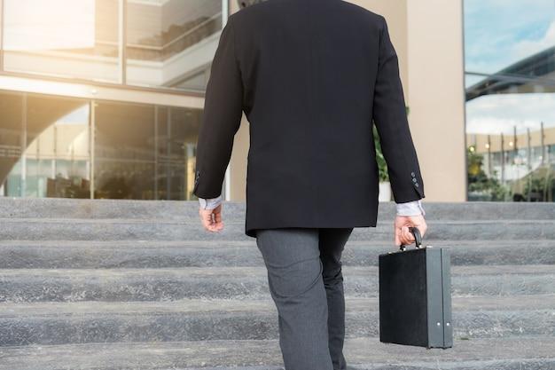 Geschäftsmann, der herauf die treppe geht und in der hand einen aktenkoffer in der arbeit arbeitet im vertrauen hält