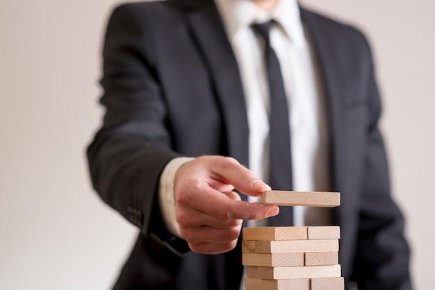 Geschäftsmann, der hölzernen domino in einen turm setzt
