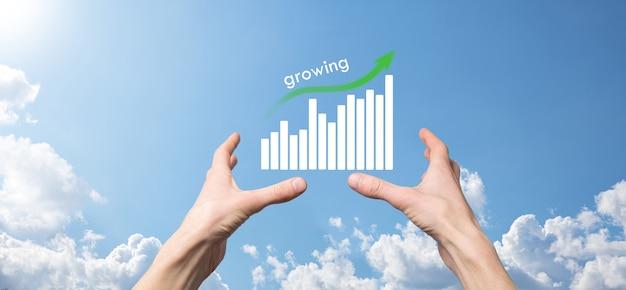 Geschäftsmann, der holografische grafiken und börsenstatistiken hält, gewinnt gewinne. konzept der wachstumsplanung und geschäftsstrategie. anzeige der guten wirtschaftlichkeit des digitalen bildschirms.