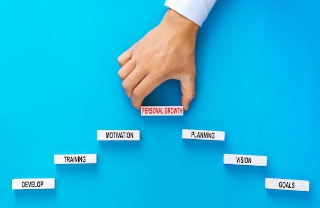 Geschäftsmann, der holzblöcke hält, die als stufentreppe mit grundlegenden verbindungen des persönlichen wachstums stapeln