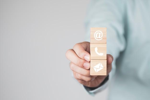 Geschäftsmann, der holzwürfelblock hält, der bildschirm druckt zeichen von e-mail, adresse und telefon für geschäftskontakt