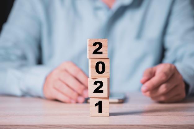 Geschäftsmann, der holzwürfelblock umdreht, um 2020 bis 2021 jahr auf holztisch zu ändern. frohes neues jahr und neues geschäftskonzept starten.