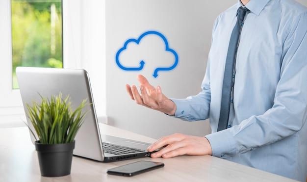 Geschäftsmann, der ikonen-cloud-computing-netzwerk und ikonenverbindungsdateninformationen in der hand hält. cloud-computing und technologiekonzept.