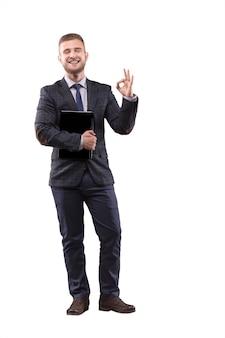 Geschäftsmann, der im anzug mit laptop in den händen steht und zeichen von ok zeigt