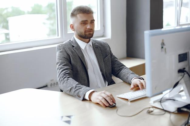 Geschäftsmann, der im büro arbeitet. mann benutzt einen computer. guy sitzt im büro