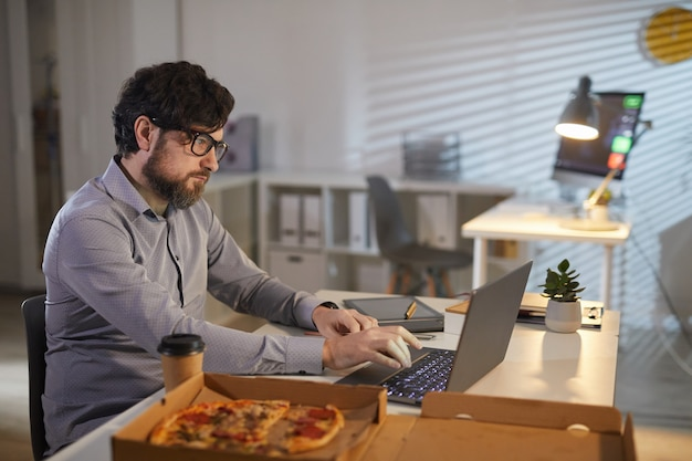 Geschäftsmann, der im büro arbeitet und isst