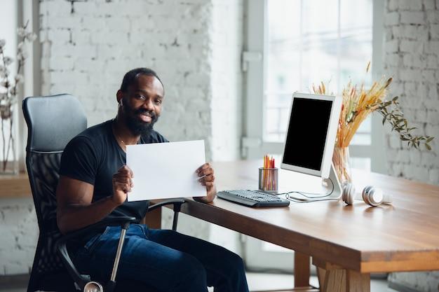 Geschäftsmann, der im büro arbeitet und leeres plakat hält