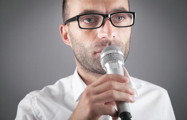 Geschäftsmann, der im büro in das mikrofon spricht.