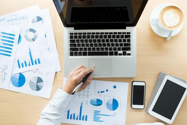 Geschäftsmann, der im büro mit laptop-, tabletten- und diagrammdatendokumenten auf seinem schreibtisch, draufsicht arbeitet