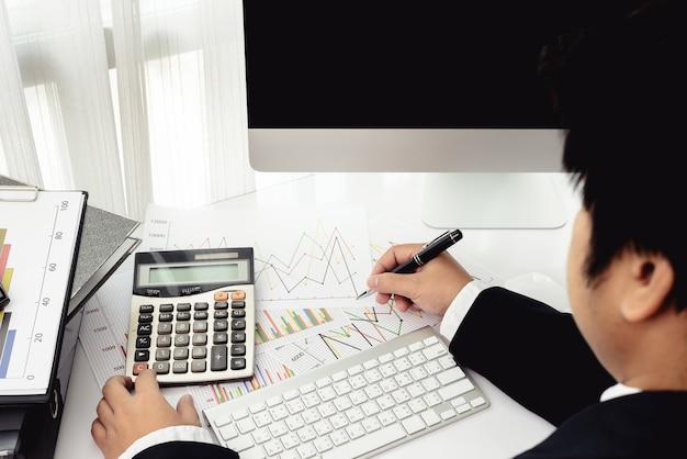 Geschäftsmann, der im büro mit tischrechner und dokumenten auf seinem schreibtisch arbeitet
