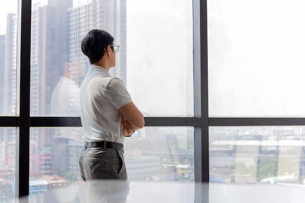 Geschäftsmann, der im büro mit verschränkten händen steht und durch fenstergebäude schaut