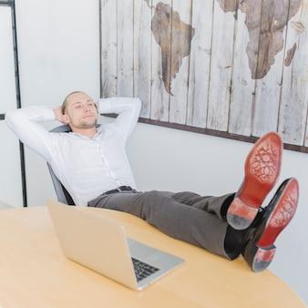 Geschäftsmann, der im büro sich entspannt