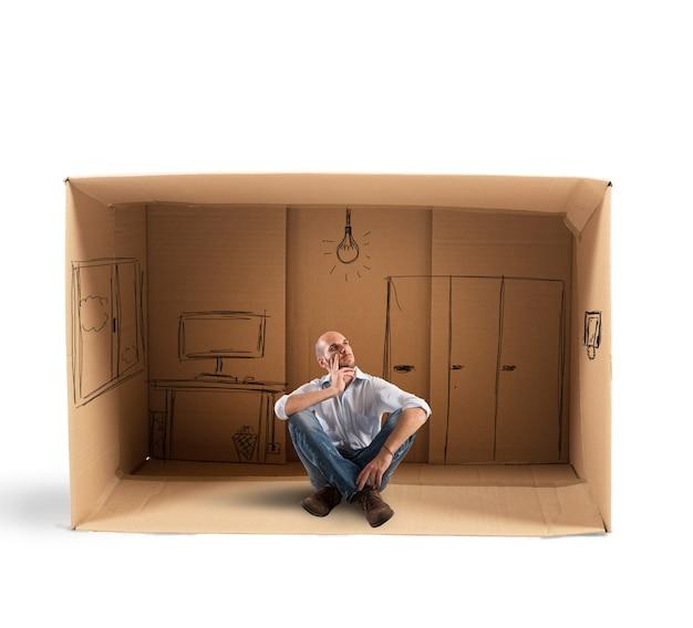 Geschäftsmann, der im büro sitzt, das im karton entworfen wird