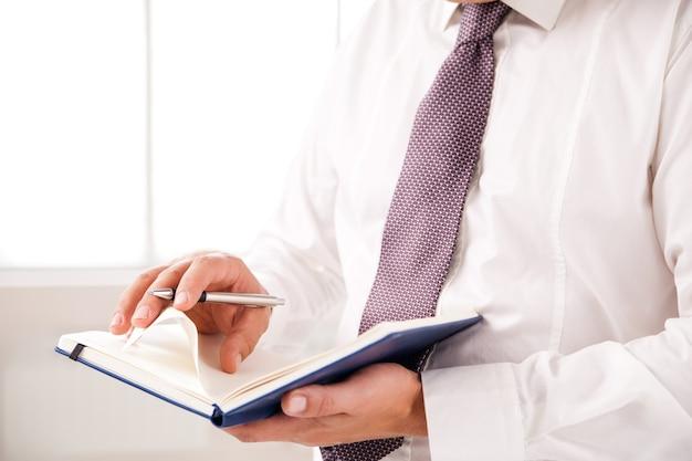 Geschäftsmann, der im büro steht und tagebuch auf weiß hält