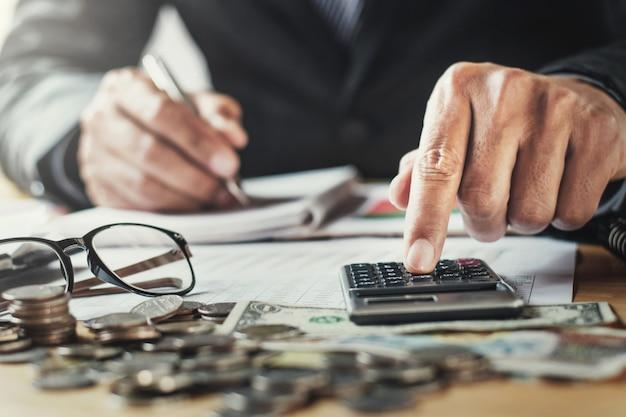 Geschäftsmann, der im büro unter verwendung des calculor für berechnen, finanzieren auf schreibtisch