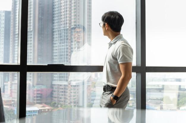Geschäftsmann, der im bürogebäude steht und durch das fenster schaut Premium Fotos