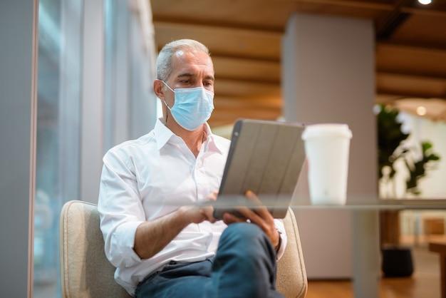 Geschäftsmann, der im café sitzt und ein digitales tablet verwendet, während er eine gesichtsmaske und eine horizontale soziale distanzierung trägt?