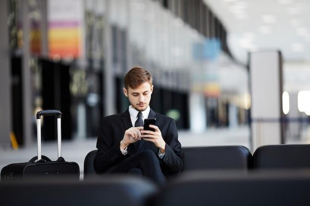 Geschäftsmann, der im flughafen wartet