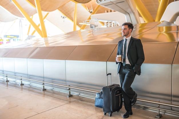 Geschäftsmann, der in den flughafen mit einem kaffee steht lächelt mit gepäck wartet