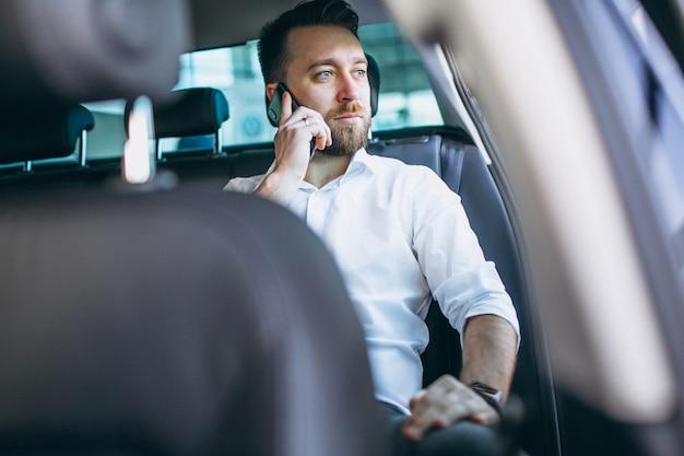 Geschäftsmann, der in einem auto unter verwendung des telefons sitzt