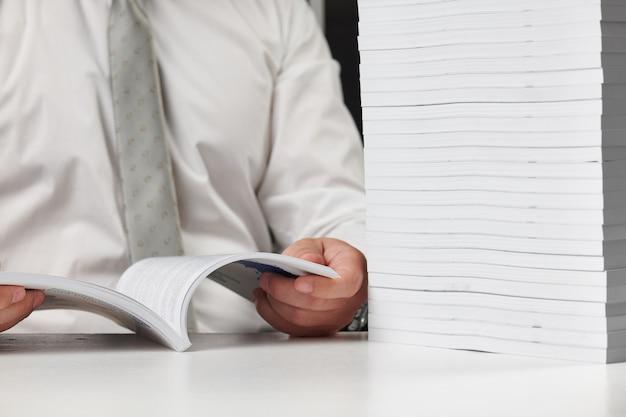 Geschäftsmann, der in einem büro arbeitet, liest stapel bücher und berichte. geschäftsfinanzbuchhaltungskonzept.