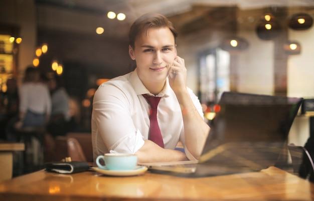 Geschäftsmann, der in einem café, unter verwendung des laptops sitzt