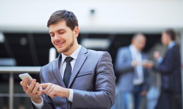 Geschäftsmann, der in einem modernen bürogebäude steht und auf ein mobiltelefon schaut