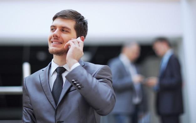 Geschäftsmann, der in einem modernen bürogebäude steht und auf einem mobiltelefon spricht