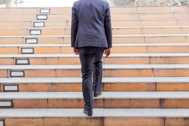 Geschäftsmann, der in einer hauptverkehrszeit die treppe hinaufgeht, um zu arbeiten. beeilen sie sich.