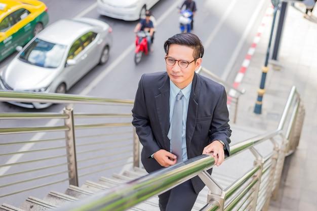 Geschäftsmann, der in einer hauptverkehrszeit die treppe hinaufgeht, um zu arbeiten.