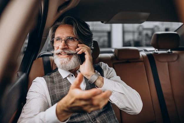 Geschäftsmann, der in seinem auto hinten sitzt