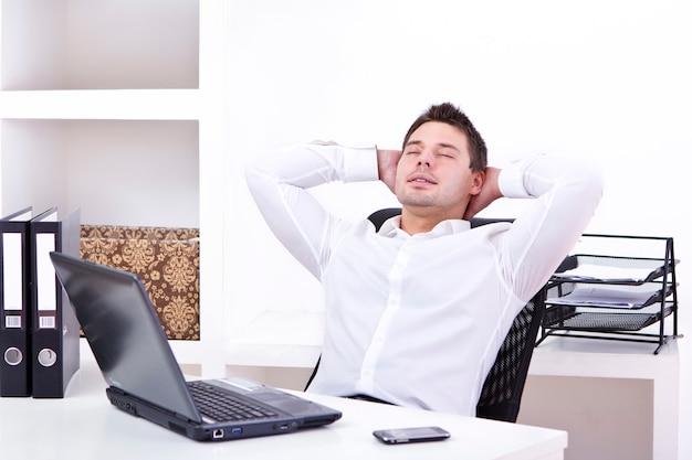 Geschäftsmann, der in seinem büro sich entspannt