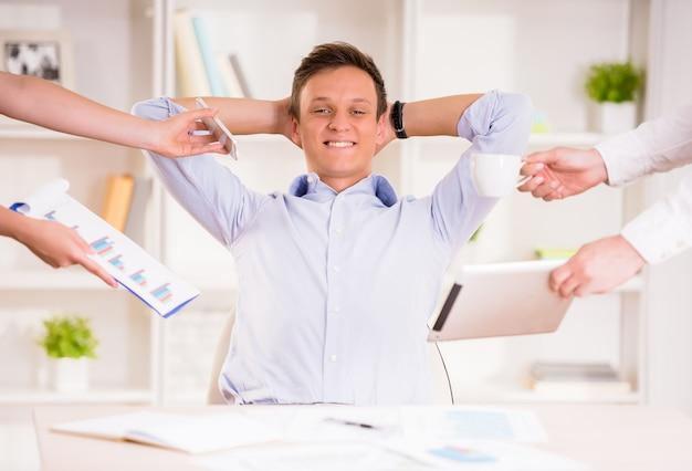 Geschäftsmann, der in seinem büro sitzt und von der arbeit stillsteht.