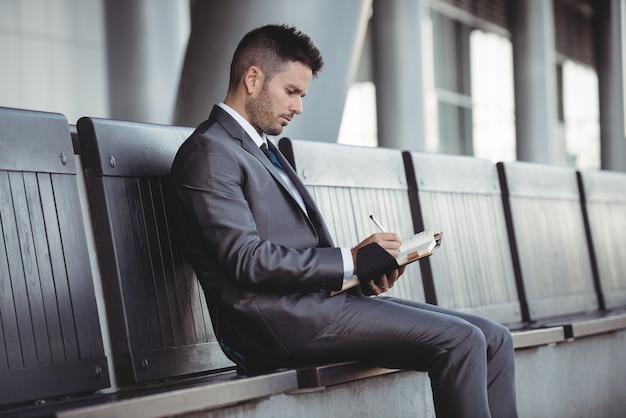 Geschäftsmann, der in seinem tagebuch schreibt, während er auf einer bank sitzt
