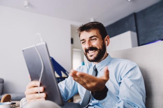 Geschäftsmann, der in seinem wohnzimmer sitzt und tablet für videoanruf während des ausbruchs von covid 19 verwendet.