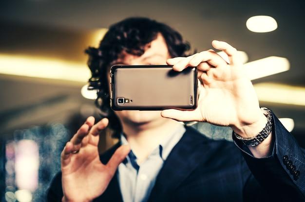 Geschäftsmann, der in smartphonebildschirm schaut