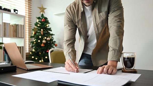 Geschäftsmann, der informationen über das dokument schreibt, während er in seinem home office steht.