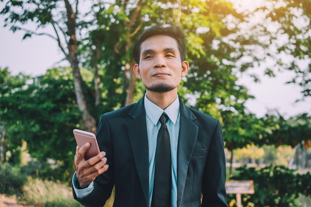 Geschäftsmann, der intelligentes mobiltelefon hält