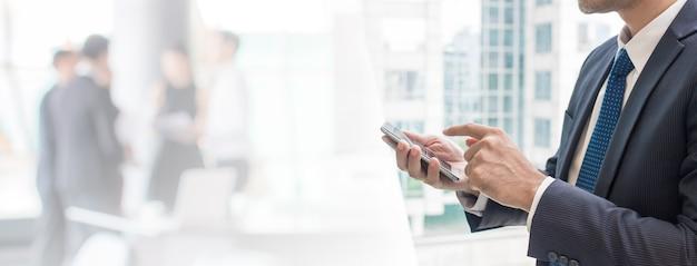 Geschäftsmann, der intelligentes telefon im büroraumhintergrund und im kopienraum verwendet.