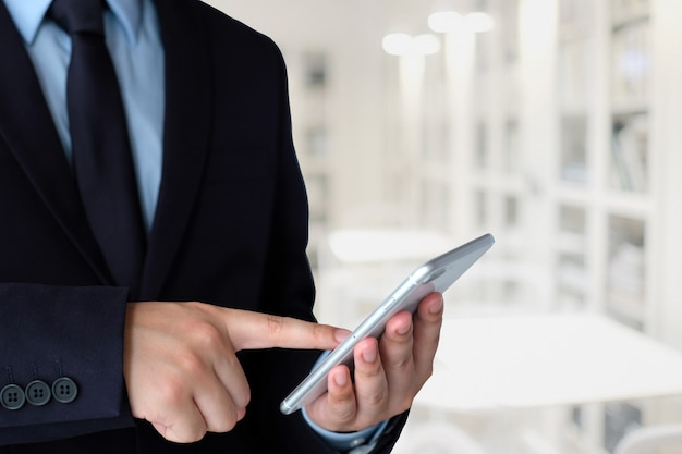Geschäftsmann, der intelligentes telefon über unschärfebürohintergrund mit kopienraum für text verwendet