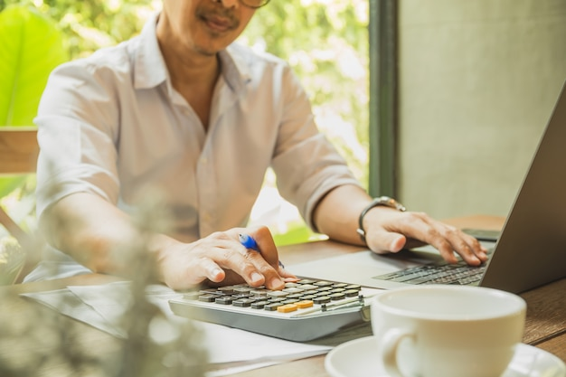 Geschäftsmann, der investition mit taschenrechner und laptop im büro analysiert.
