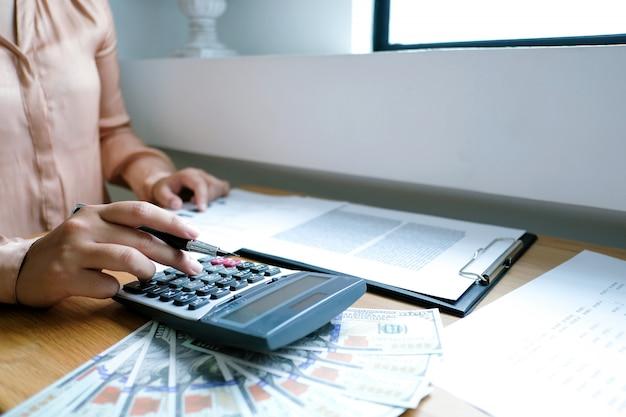 Geschäftsmann, der investitionsdiagramme analysiert und taschenrechnerknöpfe über dokumenten bedrängt