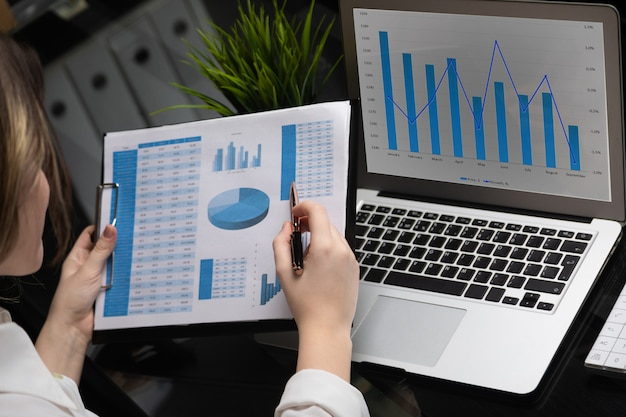 Geschäftsmann, der investitionsdiagramme mit laptop analysiert. buchhaltung
