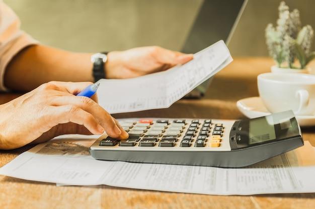 Geschäftsmann, der investitionsdiagramme unter verwendung des taschenrechners analysiert, um gewinn und verlust zu berechnen.